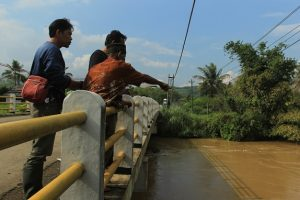 (Rubidi yang berada di tengah menunjukkan lokasi eksekusi massal di jembatan plengkung Sungai Cikawung, yang kini tinggal tersisa puingnya. Foto: KBR/Muhamad Ridlo)