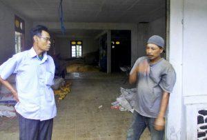 """Acep Hidayat (74) eks Tapol 65 tengah mendengarkan cerita penjaga gudang yang sering melihat """"hantu"""" menyerupai orang-orang yang disiksa dan dibunuh pada Tragedi 65 [Foto: Dok. YPKP 65]"""