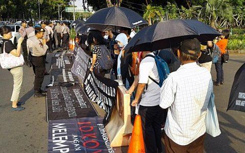 "Song So-yeon (memegang kamera) aktivis HAM pada ""The Truth Foundation"" Korea Selatan, tengah mengambil gambar pada ""Aksi Kamisan"" ke 484 di depan istana (9/3) Jakarta [Foto: Humas YPKP'65]"