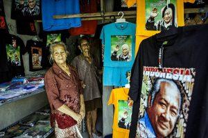 """Toko suvenir di dekat museum memiliki kaos yang menampilkan gambar Suharto yang tersenyum, di atas kata-kata ini: """"Bagaimana kabarmu, bro? Itu lebih baik di waktuku kan? """" [Kredit Ulet Ifansasti untuk The New York Times]"""