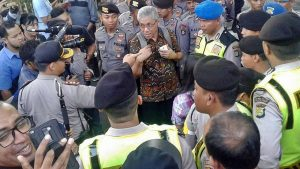 FORUM '65: Ketua Forum '65 Bonnie Setiawan tengah bernegosiasi dengan aparat kepolisian menyusul dilarangnya kegiatan seminar pengungkapan kebenaran sejarah 65 di dedung LBH Jakarta [Foto: Doc]