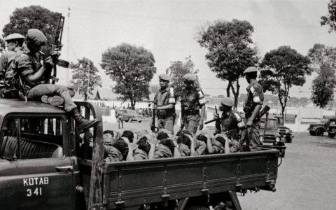 Para prajurit bersenjata mengangkut para terduga anggota Pemuda Rakyat, pada 10 Oktober 1965, dua hari sebelum diumumkannya penangkapan Letkol Untung. [BETTMANN / GETTY IMAGES]