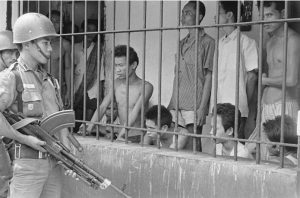 Serdadu mengawasi para tahanan yang diduga komunis di sebuah lokasi di Tangerang, Oktober 1965 [GETTY IMAGES]