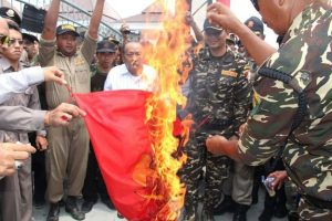 Anggota Banser, organisasi di bawah Nahdlatul Ulama, membakar bendera bergambar palu arit di Blitar, Jawa Timur, September 2015. Banser disebut sebagai kelompok 'yang turut mengeksekusi kelompok komunis'. [AFP]