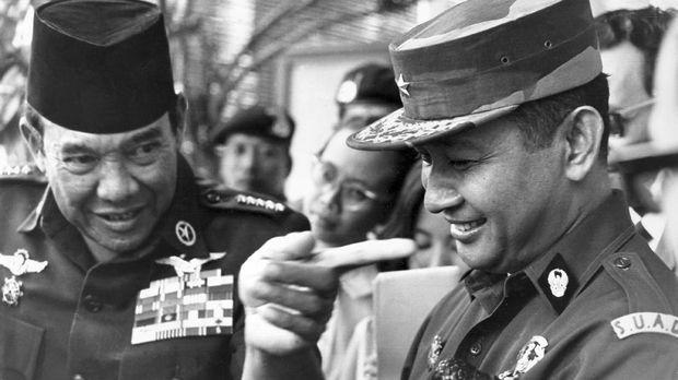 Presiden Soekarno dan periwara tinggi AD Soeharto saat berbincang, pada 1966. Kedua pihak disebut terlibat perseteruan kekuasaan melalui perstiwa 1965. (AFP PHOTO/PANASIA)
