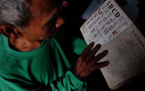 Paiman Hadi Supadmo (78) membuka buku tulisnya dari Pulau Buru. (Foto: Panji Satrio/LPM Kentingan)