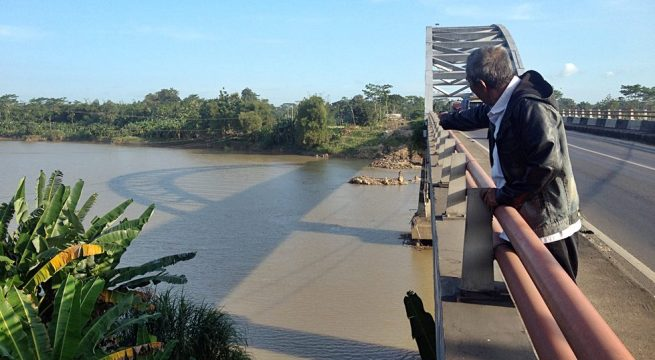 CINDAGA: Runtuhan Jembatan Cindaga yang ambrol pada 27 Juni 2011 kini tinggal puingnya. Tetapi jembatan ini menyimpan kisah tragedi pembantaian tak kurang dari 300-an Tapol 65 . Seseorang penyintas tragedi 65 menunjukkan bekas lokasi hanyutnya mayat korban pembantaian [Foto: Humas YPKP 65]
