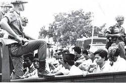 Para anggota Pemuda Rakyat (sayap pemuda PKI) dijaga oleh para tentara dalam perjalanan mereka dengan truk bak terbuka ke penjara pada tanggal 30 Oktober 1965.
