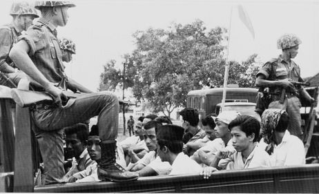 Members of the Youth Wing of the Indonesian Communist Party (Pemuda Rakjat) are guarded by soldiers as they are taken by open truck to prison in Jakarta, Oct. 30, 1965.  Credit: AP Photo