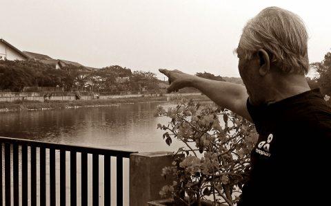 KAMP KERJAPAKSA: Dari arah sebrang sungai Cisadane, Bedjo Untung menunjukkan eks lokasi kamp kerjapaksa yang terbentang seluas 110 hektar dan terbagi dalam 2 blok yang berbeda. Sebagaimana diketahui, Bedjo Untung pernah dipenjara di RTC Tangerang dan menjadi pekerja paksa di kamp Cikokol ini [Foto: YPKP65/Humas}